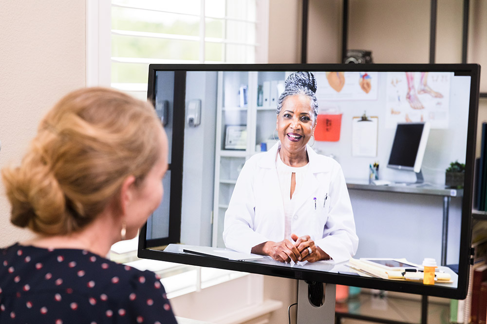 A mid adult woman who is sheltering in place video conferences with her mature adult female doctor.